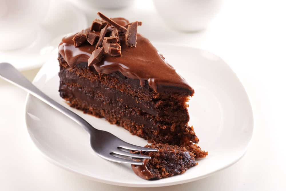 A dessert fork resting on a white dessert plate with a slice of chocolate cake.