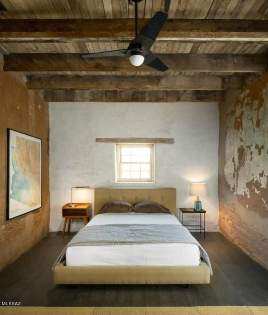 Another bedroom features a regular bed with a couple of table lamps on both sides and a wall decor.