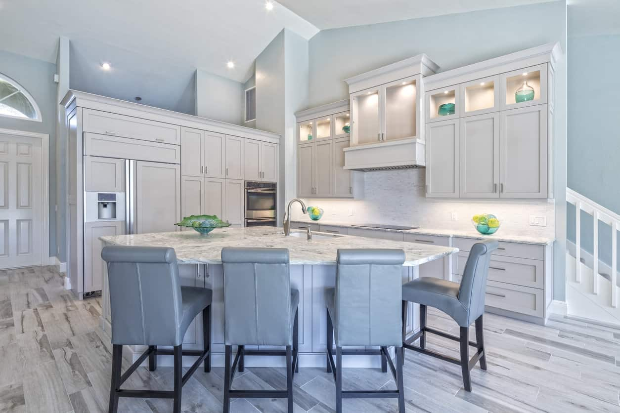 Fabulous light blue and white kitchen with vaulted ceiling, recessed lighting and pie-shaped island with sumptuous blue leather upholstered island stools. The light, aged looking wood floor is a perfect match for this kitchen color scheme.