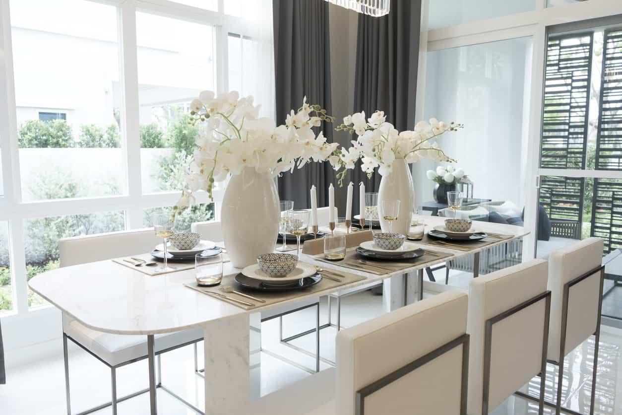 Bright modern dining room with a dainty looking dining table with marble legs (interesting). Notice how thin the table top is plus the rounded corners. The table gains some heft with the large vases filled with white flowers. The room enjoys plenty of light from the floor-to-ceiling windows.