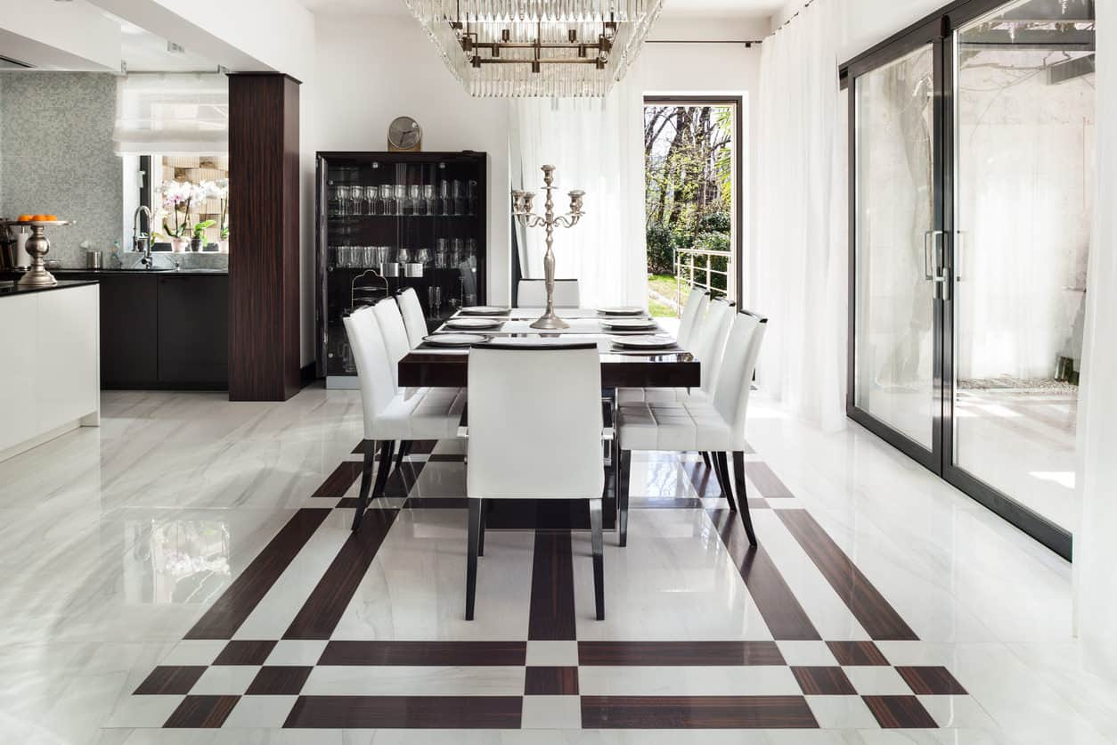 Glamorous white and black dining room with black table (accommodates 8 people) rimmed with 8 white and black comfortable dining chairs. The custom floor includes white and black pattern to match the dining room furniture. Very glamorous.