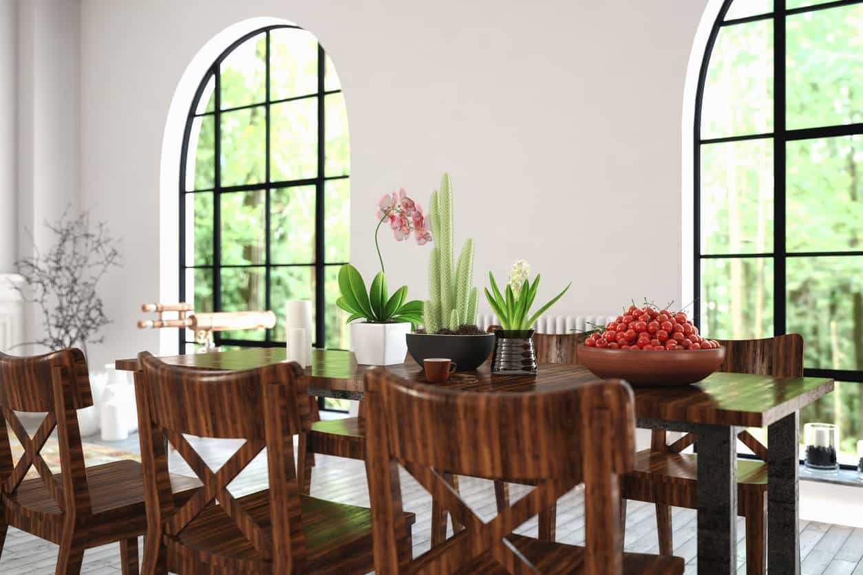 Close up of dark wood dining table and chairs in large open dining rooms space with all white walls, beautiful arched windows matched with beautiful plank wood flooring.