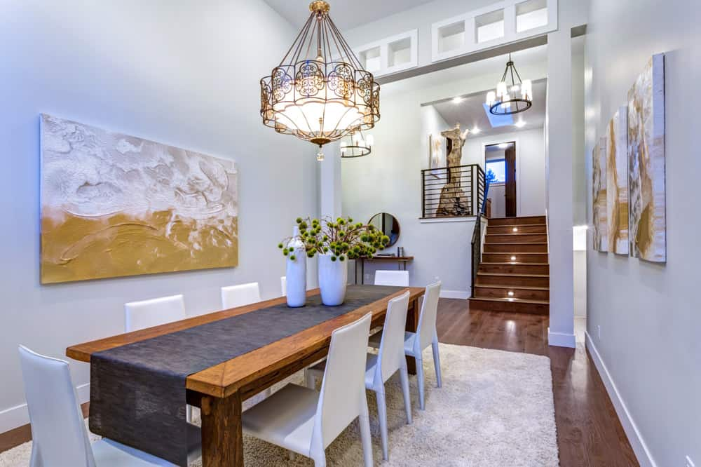 Enclosed dining room with very tall ceiling. Off-white walls match the dining room chairs which is contrasted with a medium dark table and flooring. Off-white plush area rug sits squarely below the table.