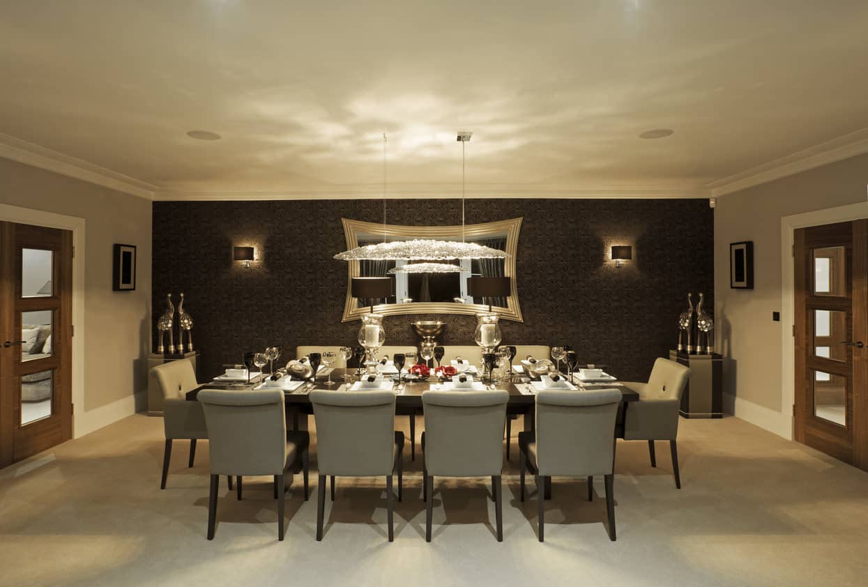 Spacious enclosed formal dining room with black accent wall that contains two wall lights and large mirror. The dining table is dark wood and has large, comfortable upholstered dining chairs that can accommodate 10 people.