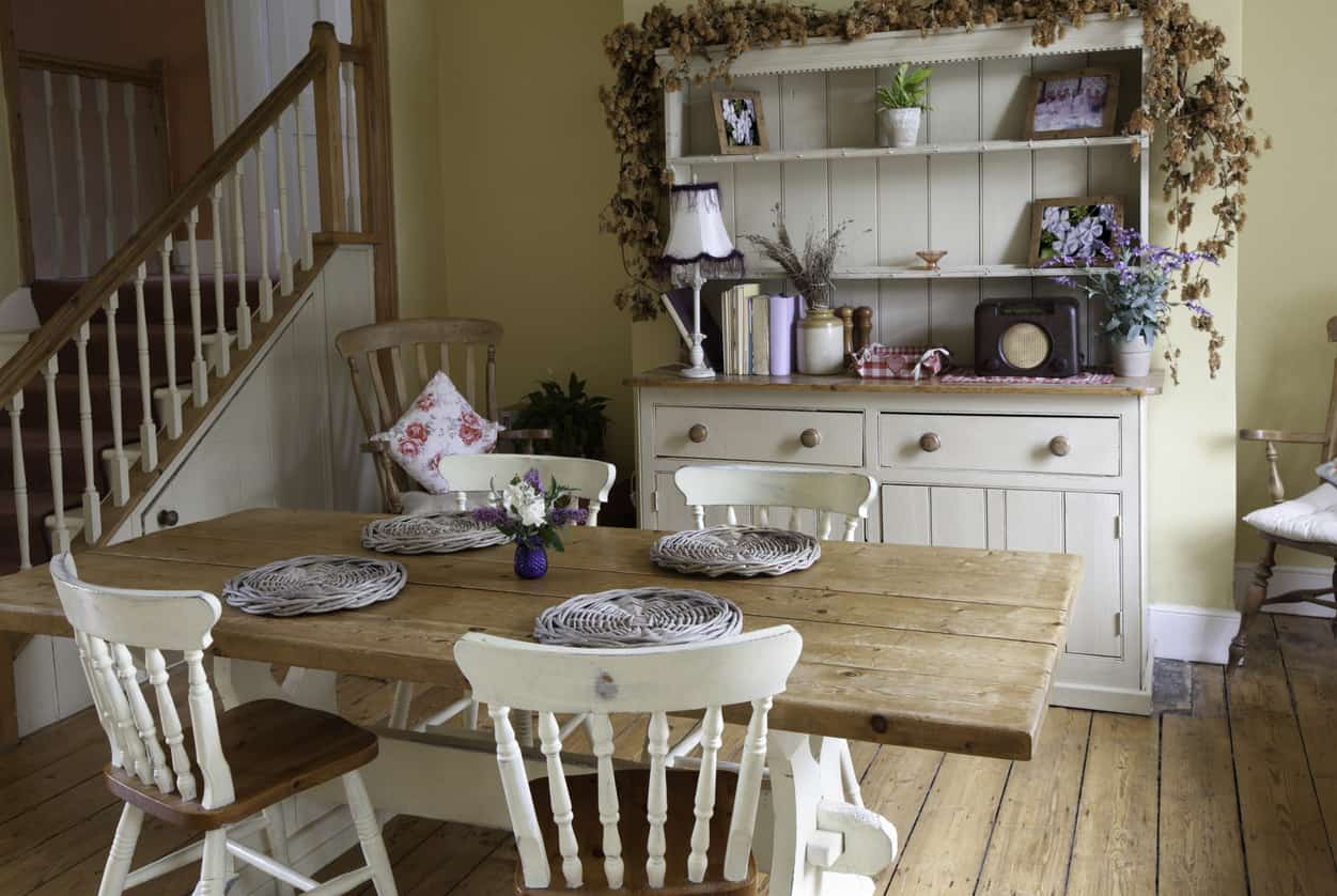 Wonderful example of a small farmhouse style dining room with brown and wood chairs and quintessential farmhouse dining table with visible plants and white painted base. A white buffet sits on the side adjacent to a wood rocking chair. Notice the thick wood plank flooring which fits in with this farmhouse style dining room.