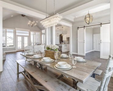 Light rustic dining room table with bench seating in large dining rooms space. Long chandelier suspended above the table in new custom built home.
