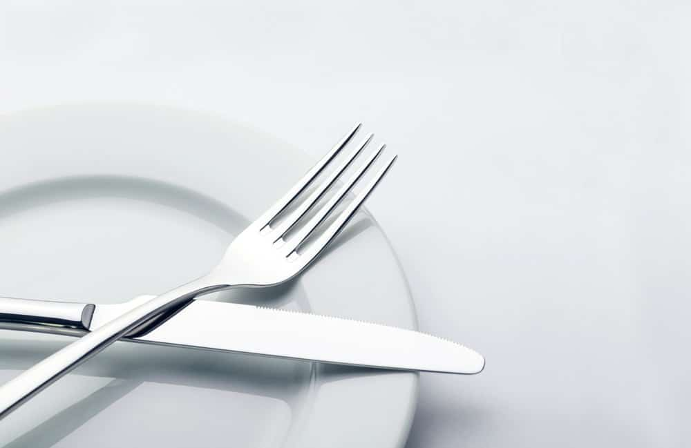 Dinner fork and knife on white dining plate.