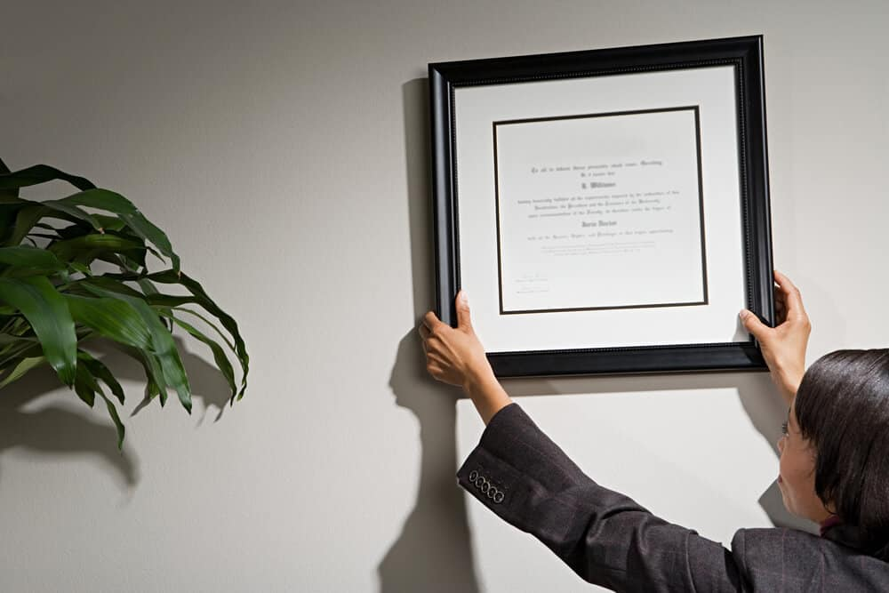 A woman hanging a document picture frame on the wall.