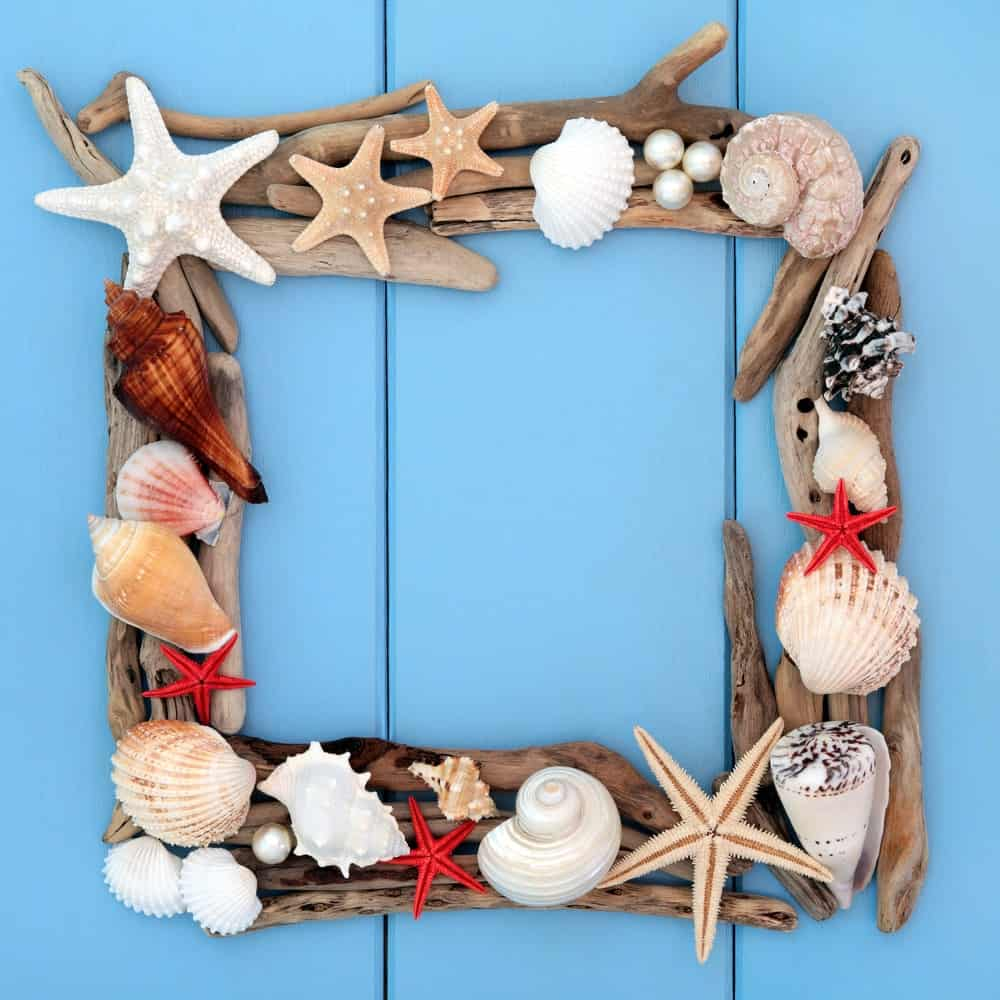 DIY picture frame made of starfishes, seashells, and driftwood on blue wooden background.