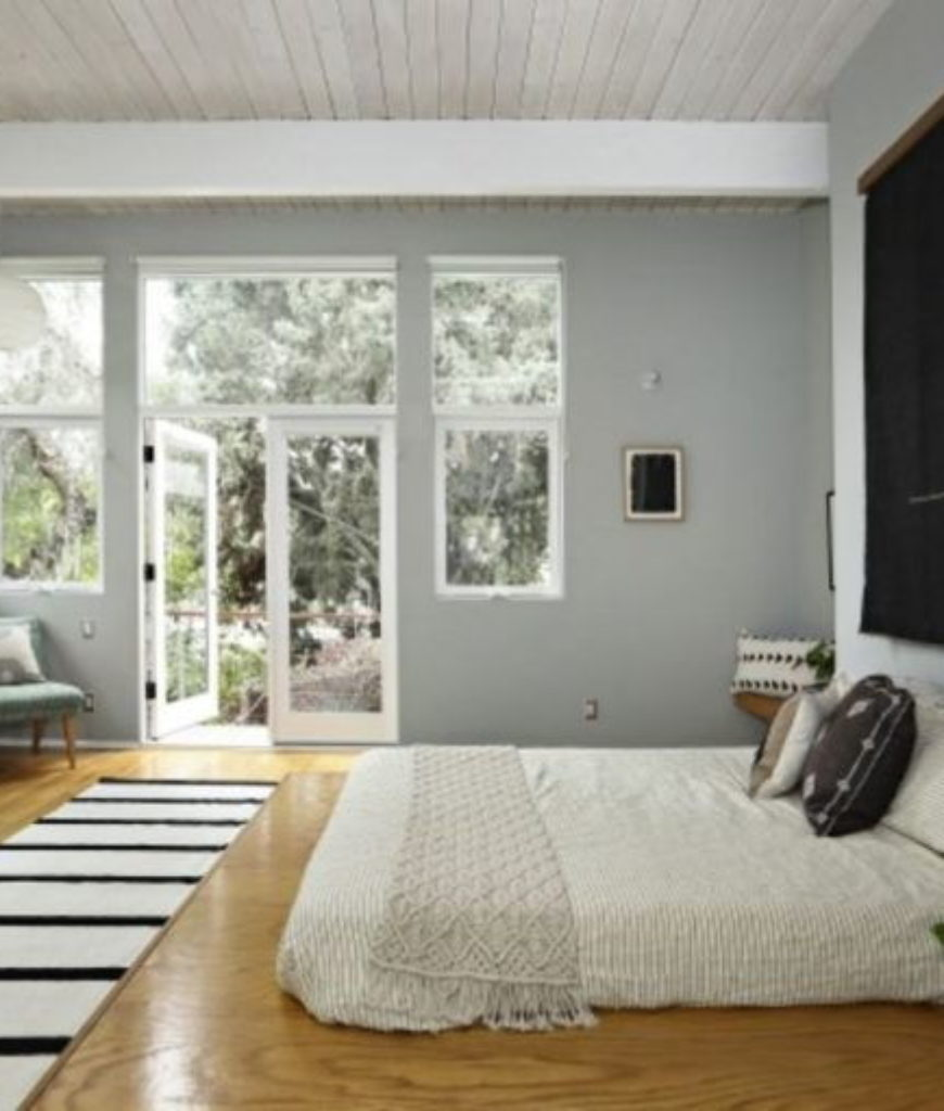 The bedroom features laminated flooring, large bed, gray walls and a stylish wall decor.