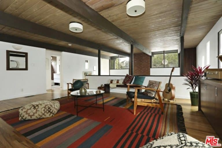 A striking striped rug lays on the natural hardwood flooring in this living room with a glass top coffee table and cozy seats illuminated by a pair of white flush lights mounted on the wood beam ceiling.