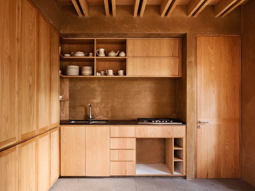 This kitchen features a walnut finished cabinetry and kitchen counters matching with its walls and ceiling.