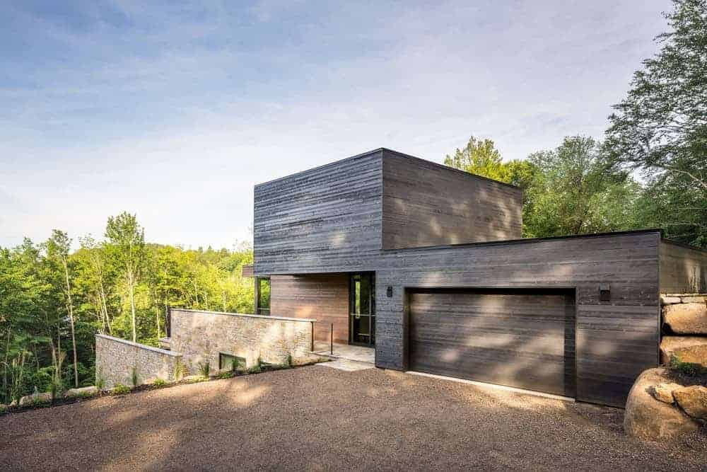 A large modern home with a wooden exterior painted in black.