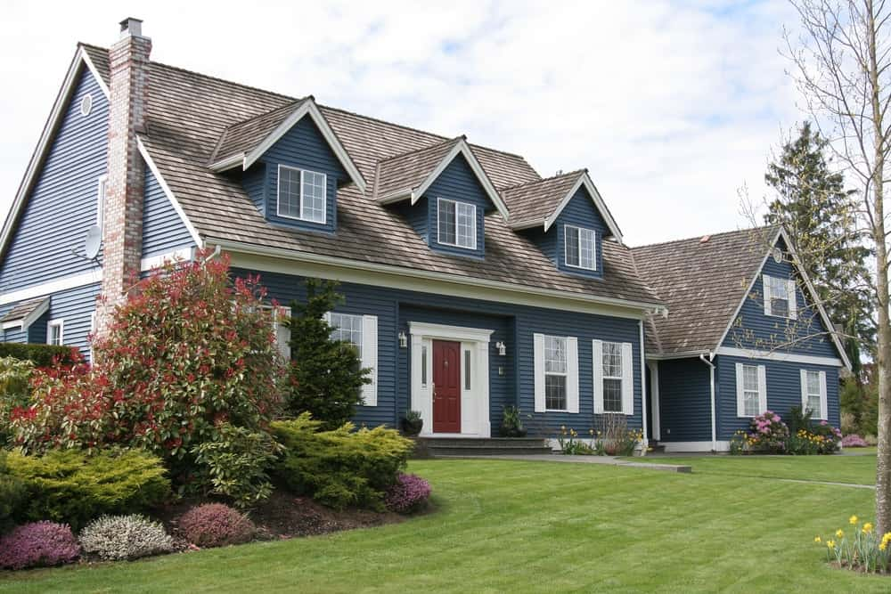 The textured theme of this executive house starts from its dark shingles and down to the brick chimney and blue exterior siding. White trims offset with a coolness and softness and also used to set off the red front door that adds a touch of warmth.