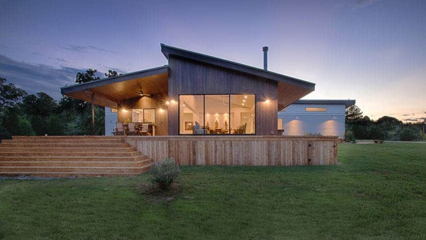 A wooden home featuring a spacious deck and a sprawling lawn area.