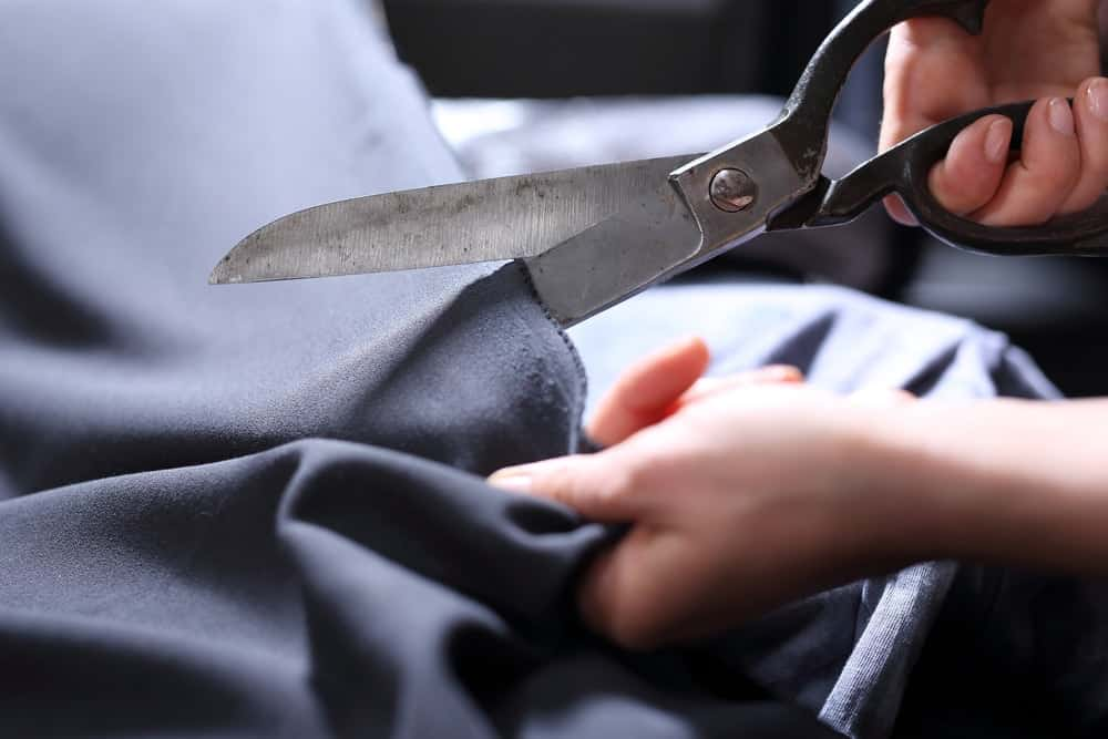 The stainless scissors is being used to cut through fabric.