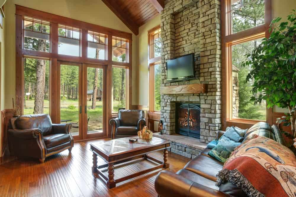 A large family room with comfy sofa seating and fireplace in hardwood flooring and glass windows.