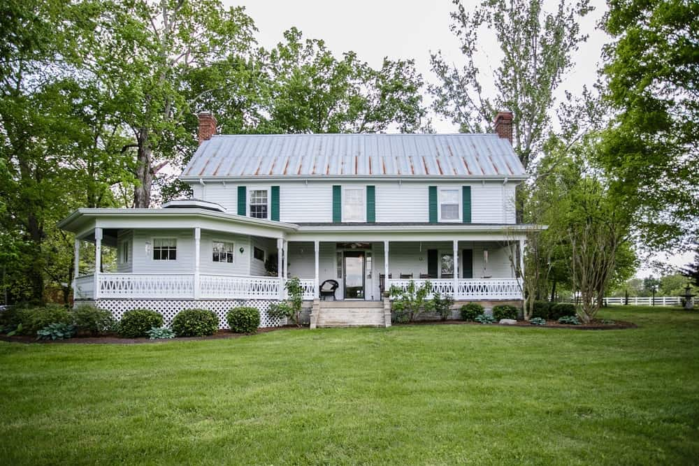 Countryside farmhouse with big lawn, long front porch, and multilevel interiors.
