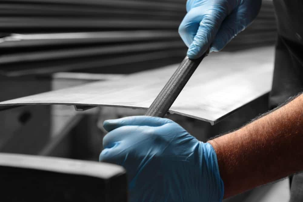 A laborer is using a file to smoothen the edges of a metal.