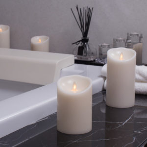 Flameless battery-powered candles on bathtub ledge