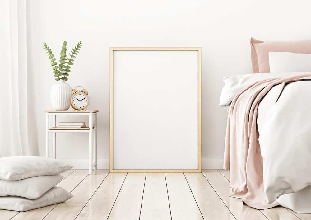 A big picture frame on the bedroom floor.