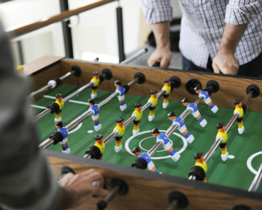 Two people playing foosball, one in the yellow team and the other in the blue team.