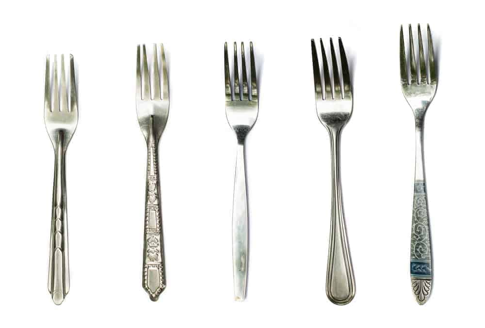 A collection of stainless steel forks on white background.