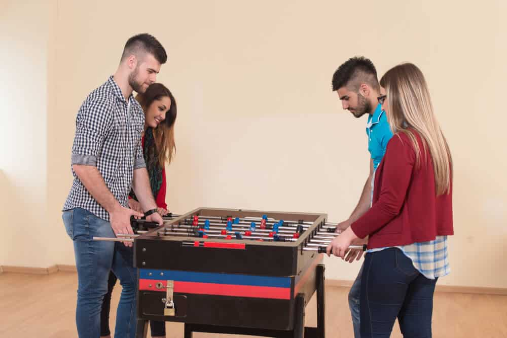 Four people playing Foosball.