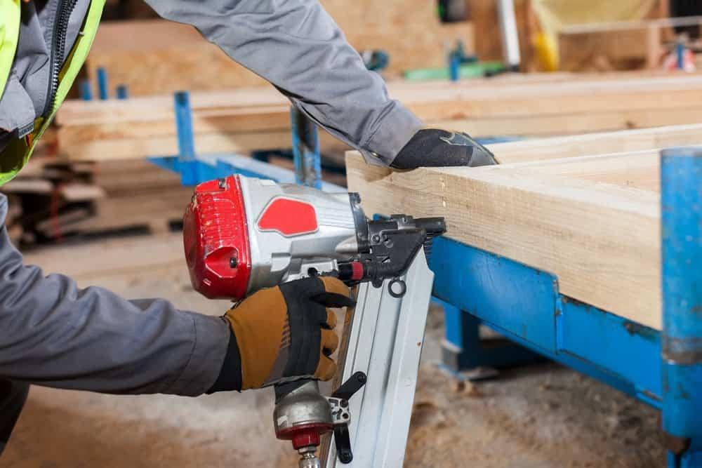 A framing nailer is being used to join wooden boards.