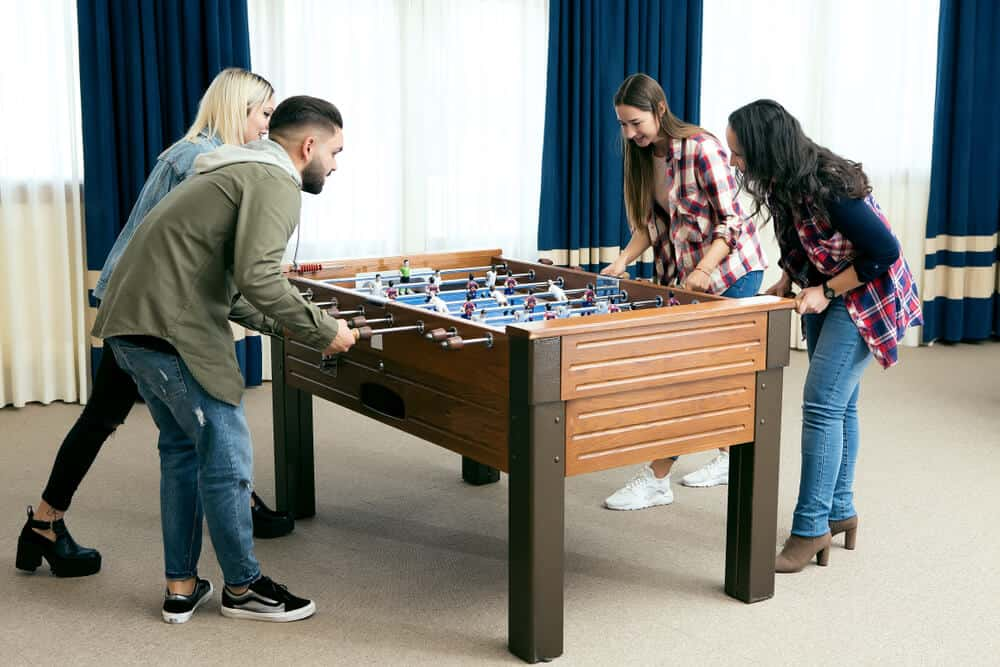 A freestanding foosball table played by friends.