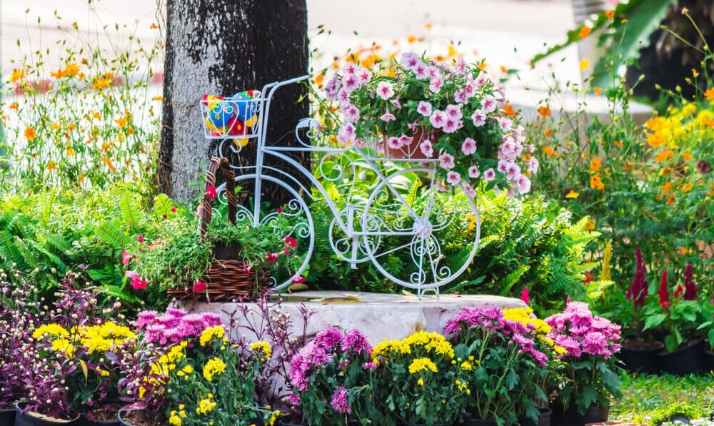 A garden with lots of flowers and an old, white bicycle assembles as a decoration.