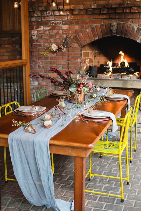 Cloth gift wrap used as a table runner on wooden dining table with yellow Shabby-Chic chairs with brick fireplace nearby and brick flooring