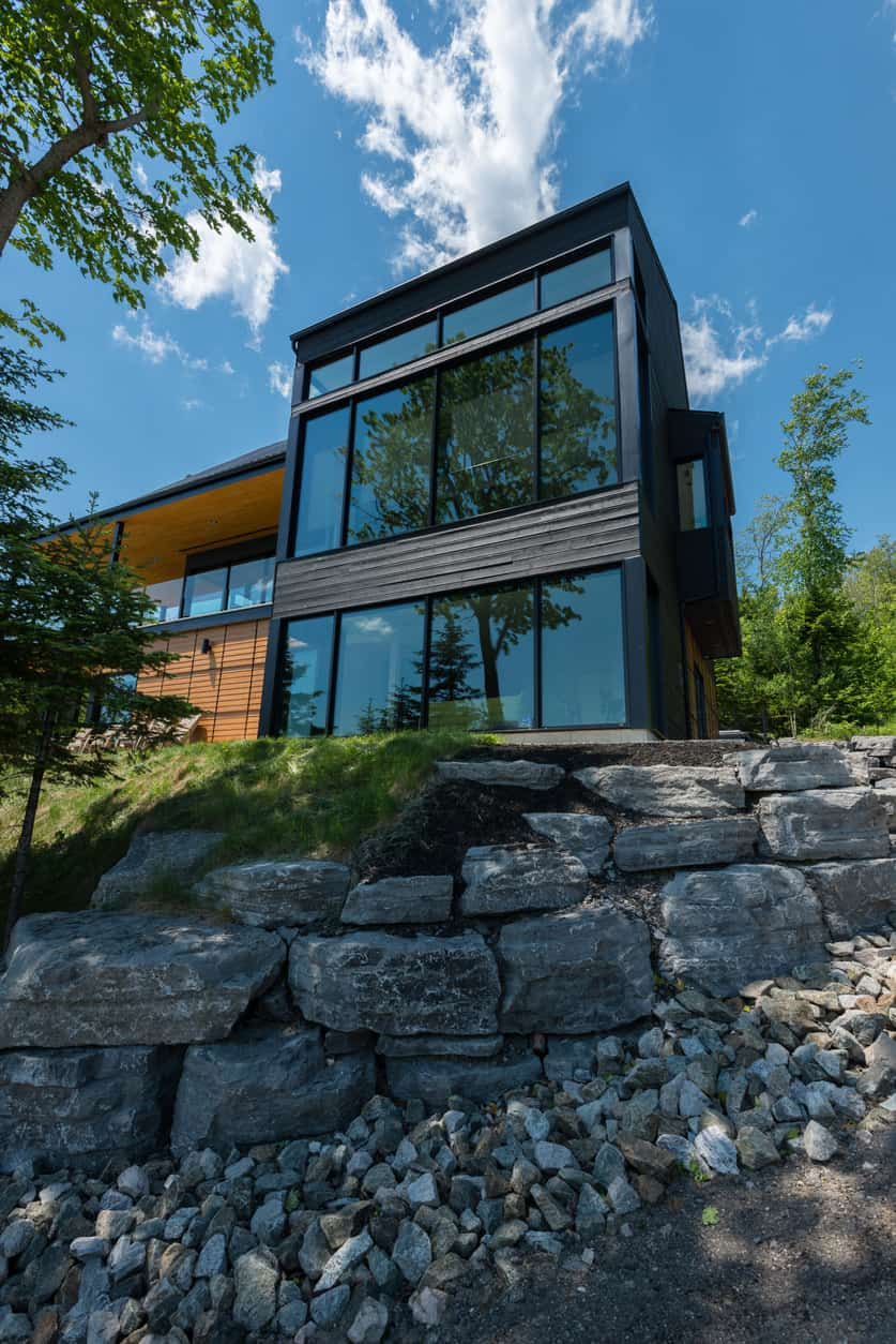 Cliff-side home with two story towering glass section overlooking the steep property.