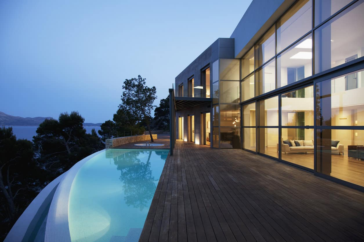 Cliff-side mansion with extensive glass rear (2 story glass walls) overlooking infinity pool and wood deck.
