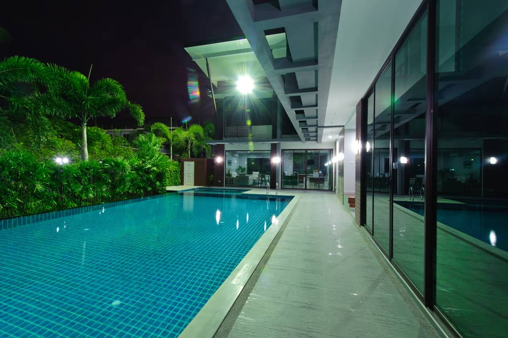 Modern mansion at night with extensive glass spanning length of home overlooking private pool and deck area.