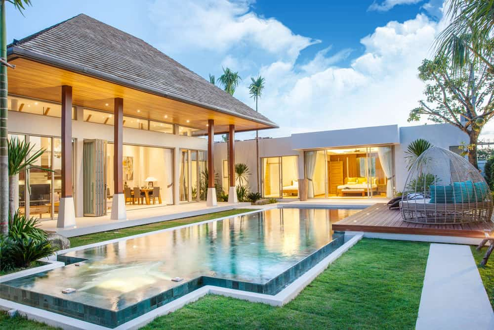 Classic tropical villa home where almost every square foot of the L-shaped home is floor-to-ceiling windows overlooking the gorgeously manicured backyard with pool.