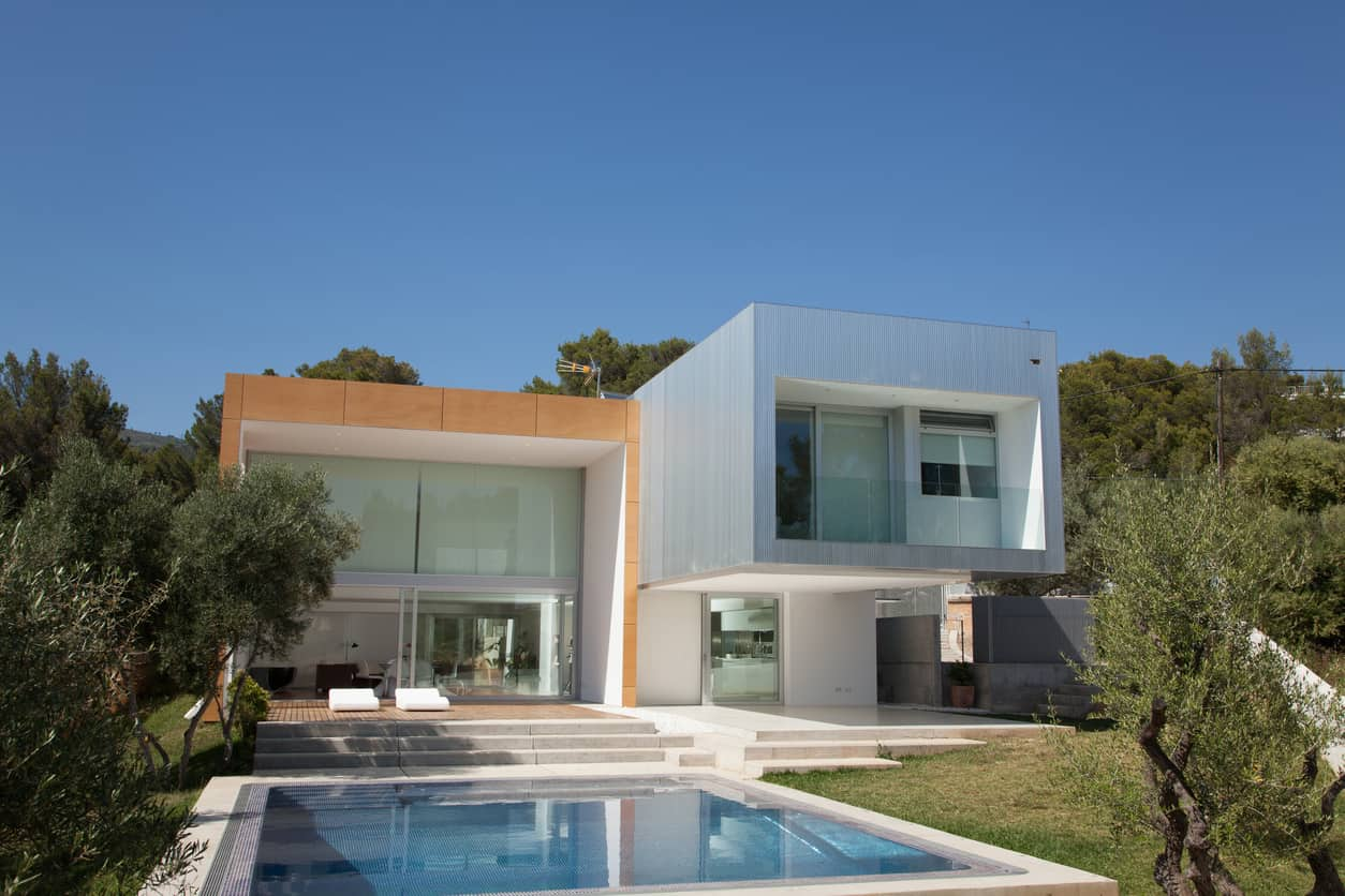 Modern home in warm climate with huge windows on 3 of 4 sections overlooking the property including small square pool.