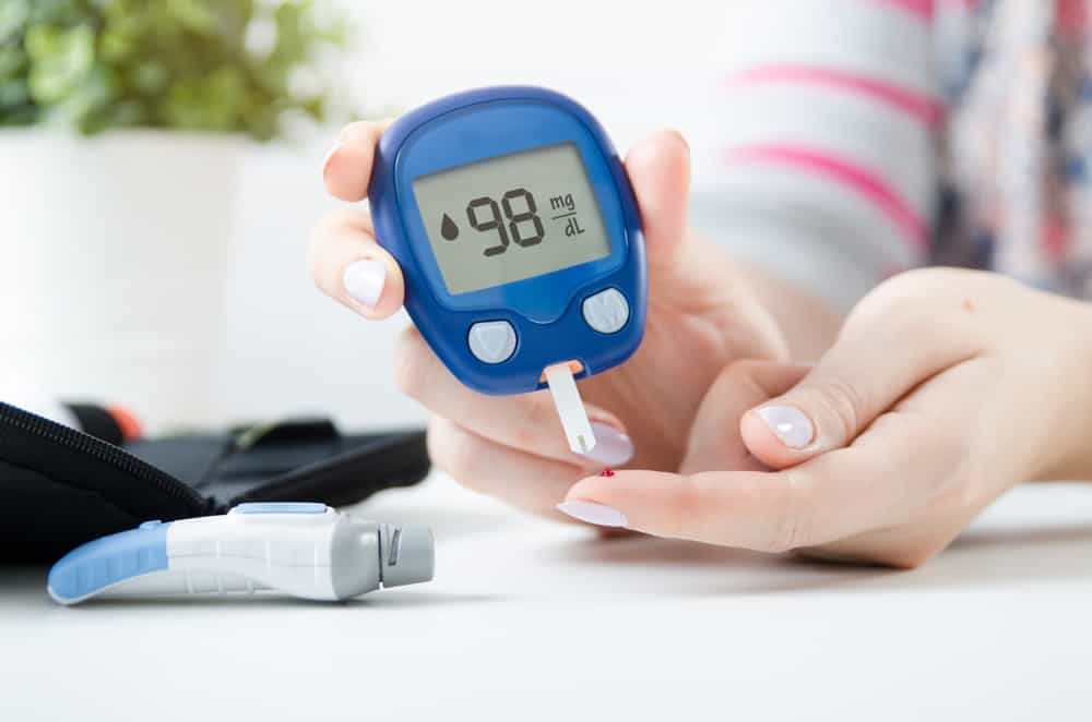 A lady is using a digital glucometer to check her blood sugar level.