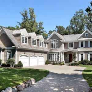 gorgeous long driveway leading up to custom built new mansion with three car garage