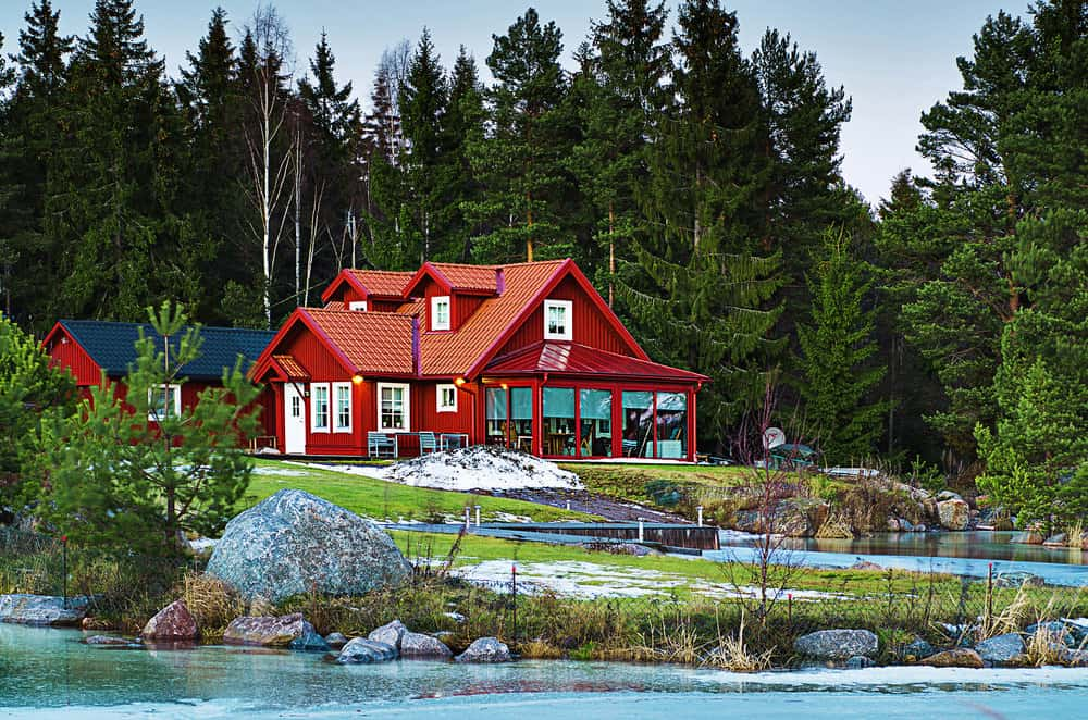Quintessential red waterfront country home in Sweden with sunroom surrounded by forest. The red exterior includes white trim windows and a white front door.