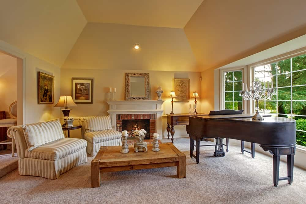 An impressive grand living room with piano and carpet flooring, great for hosting larger parties and events.