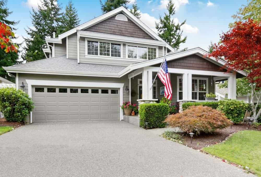 Country style house with grey exterior and has a porch and a garage along with colorful trees.