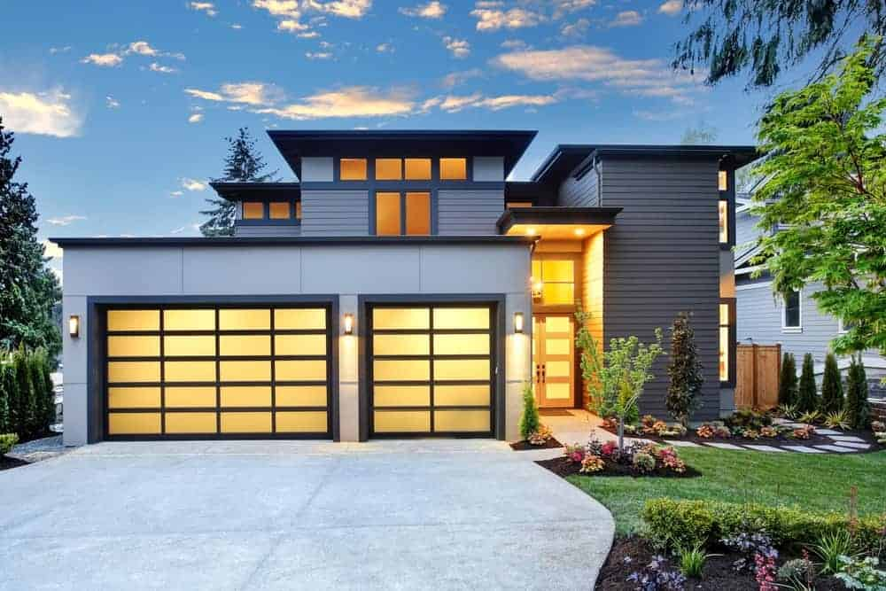 Modern house with grey exterior featuring its modish driveway and garden.
