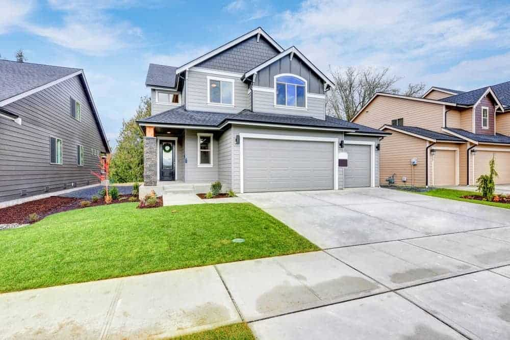 House with grey exterior and small garage along with small garden area.