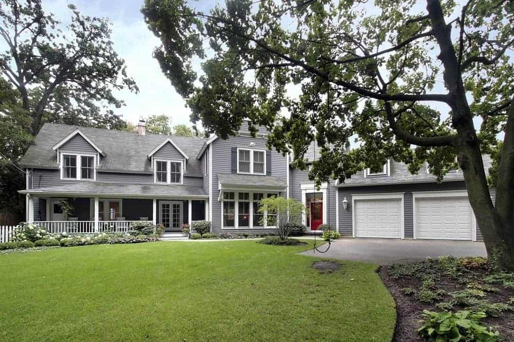 House with grey exterior featuring large porch area and garden along with a garage.