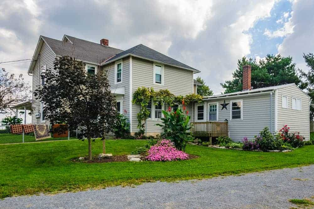 House with grey exterior featuring its beautiful garden and well-maintained lawn.