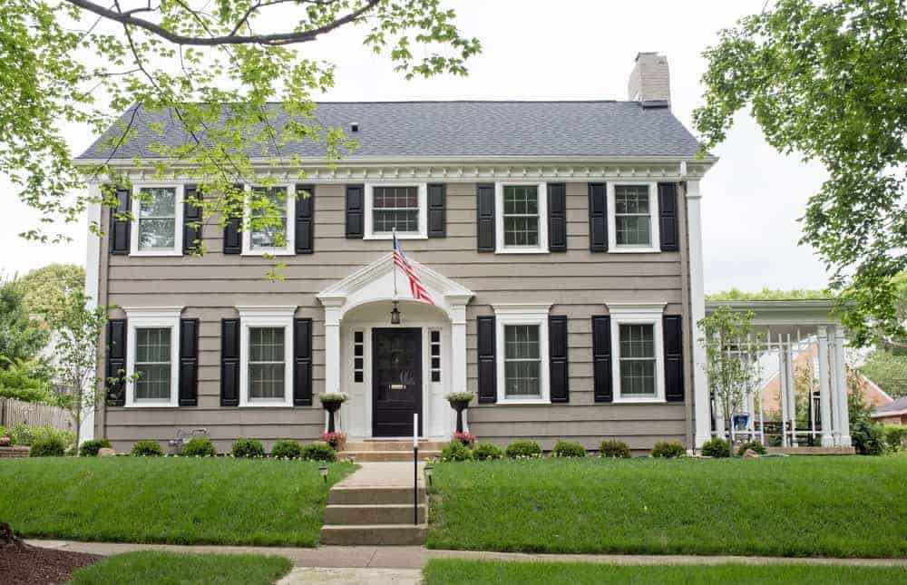Large house with grey exterior and beautiful, well-maintained lawn.
