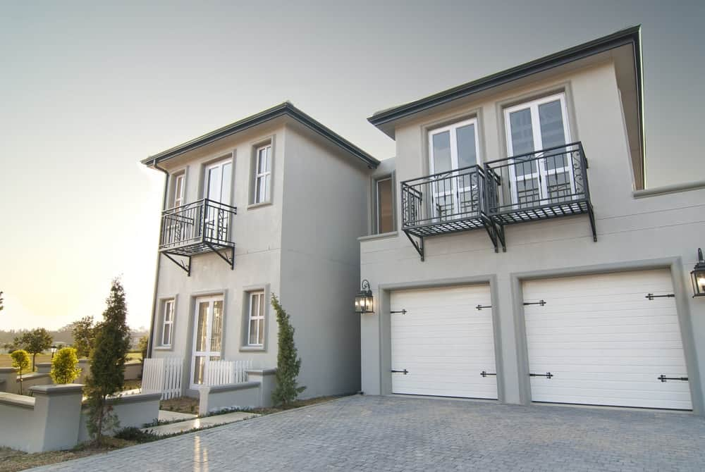 Two-storey house with grey exterior featuring its backyard and garage.