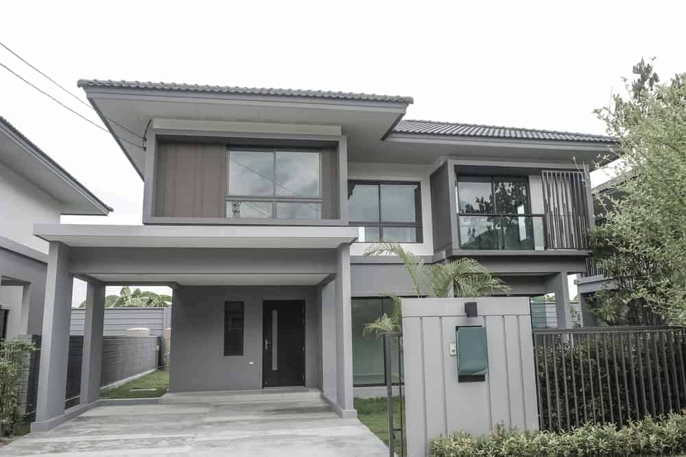 Modern house with grey exterior featuring its open garage and a garden area.