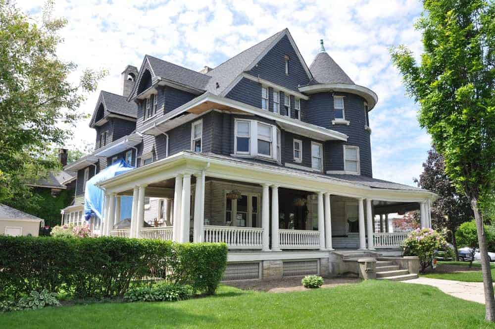Large three-storey house with grey exterior featuring its wide deck porch and garden area.